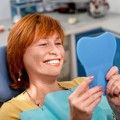 A mature woman with red hair looking at a blue mirror after her cosmetic dentistry appointment