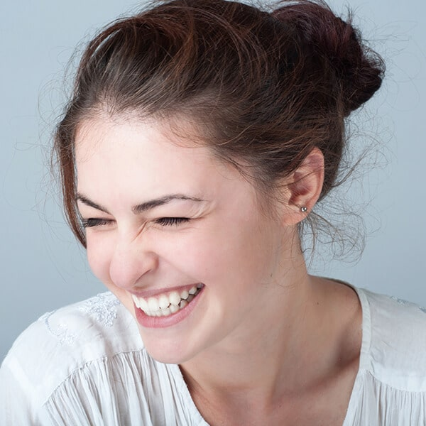 A brown-haired woman laughing while wearing a white shirt
