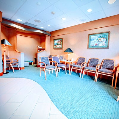 The waiting room at our dentist in Redmond WA, showing the chairs, pictures, and a light blue mat
