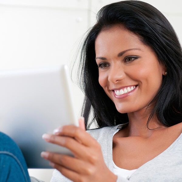 A woman lying while holding a tablet and smiling
